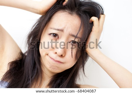 young girl scratching her hair - stock photo