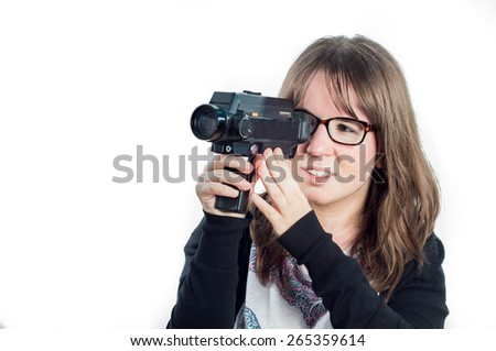 Young girl shooting with super 8 camera with glasses isolated on white background - stock photo