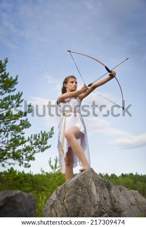 young girl shoots a bow from a high cliff in the forest - stock photo