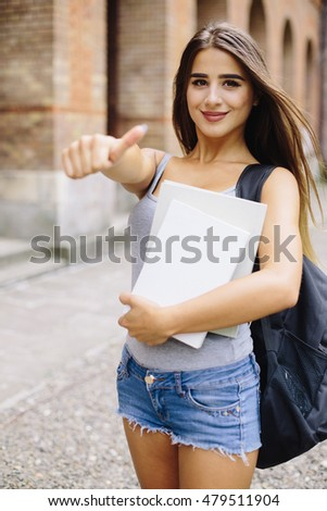 Young girl show ok gesture that study in University is good