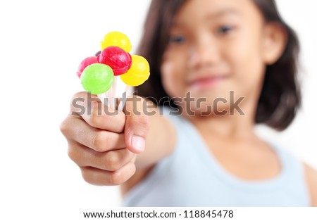 Young girl showing a sweet and colorful lollipops. - stock photo