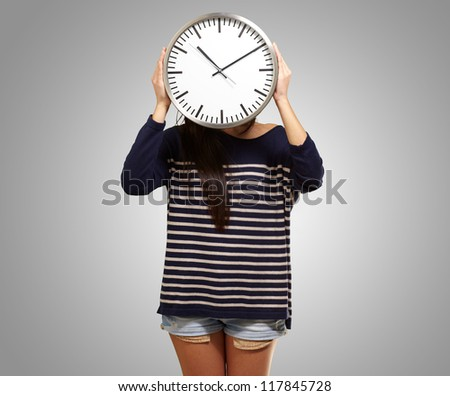 Young Girl Showing Clock And Hiding Her Face On Gray Background