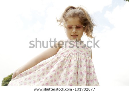 Young girl showing off her dress and wearing pink shades.