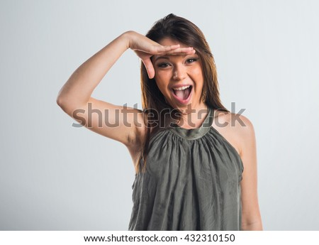 Young girl showing something over grey background