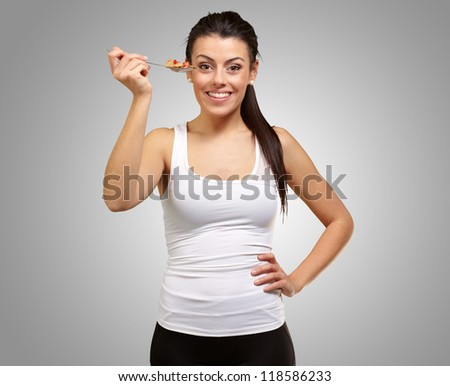 Young girl showing spoon full of cornflakes isolated on gray background