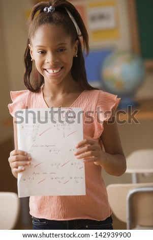 Young girl showing test score of 100 - stock photo