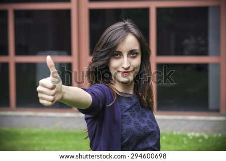 Young girl showing thumbs up gesture - stock photo