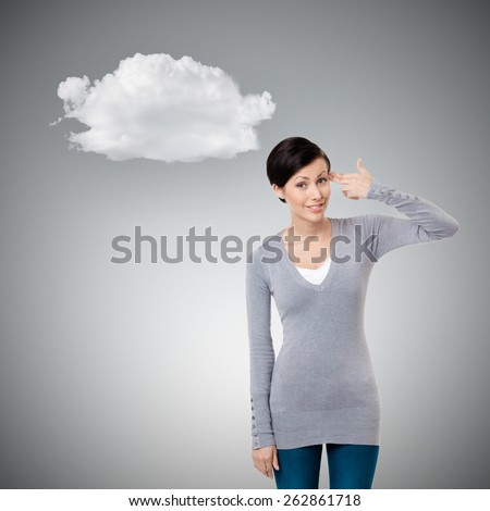 Young girl shows hand gun gesture, isolated on grey - stock photo