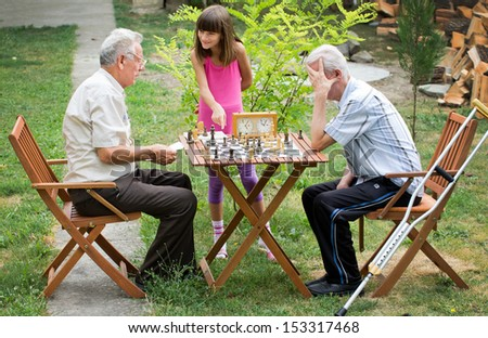Young girl shows pensioners how to play chess - stock photo