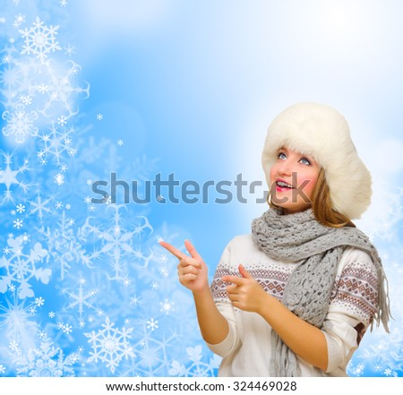 Young girl shows pointing gesture on winter background - stock photo