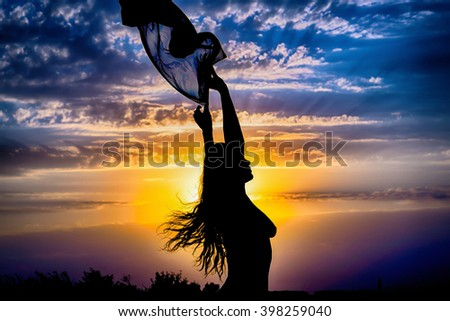 Young girl silhouette with shawl on background of beautiful cloudy blue sky with yellow golden sunset and rays of light HDR effect - stock photo