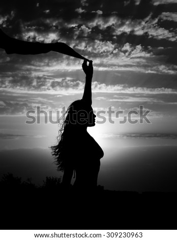 Young girl silhouette with shawl on background of beautiful cloudy sky with sunset and rays of light black and white
