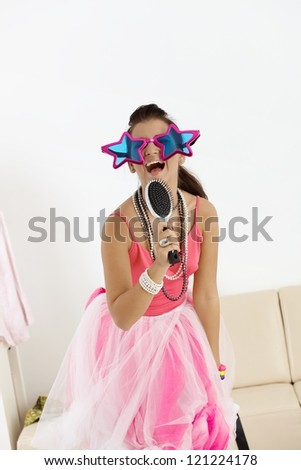 Young girl singing at home in fancy-dress and funny glasses. - stock photo