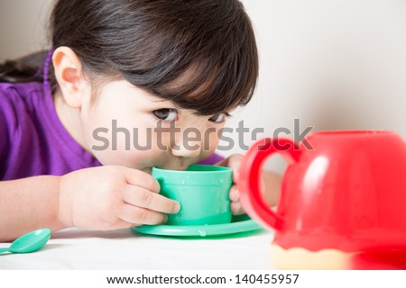 Young girl sipping from her cup having a tea party