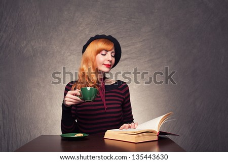 young girl sitting and a reading a book while drinking her coffee on grunge background - stock photo