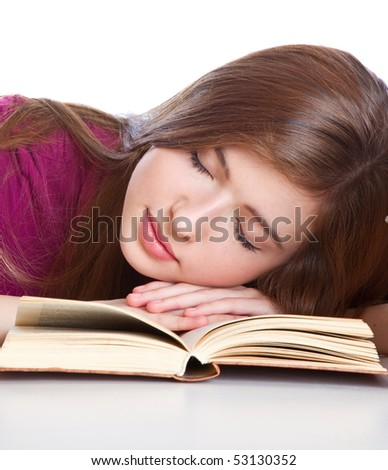 Young girl sitting at the desk and sleeping on a book. Isolated on white background
