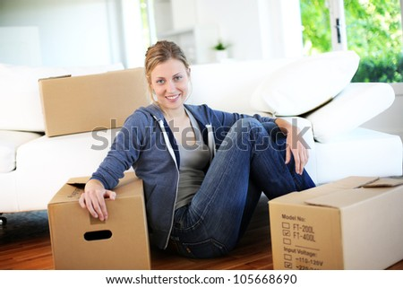 Young girl sitting by cardboards in new home - stock photo