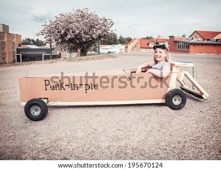 Young girl sitting in a soap-box car shaped like a piece of pumpkin pie. - stock photo