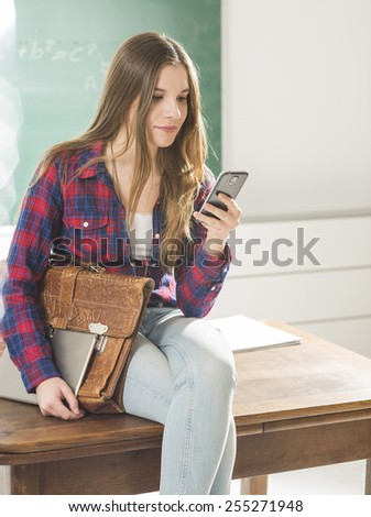 Young girl sitting in class room with tablet and phone - stock photo