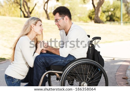 Young girl sitting in front of her boyfriend in a wheelchair in the park - stock photo