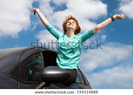 young girl sitting in the car and holding a key against blue sky  - stock photo