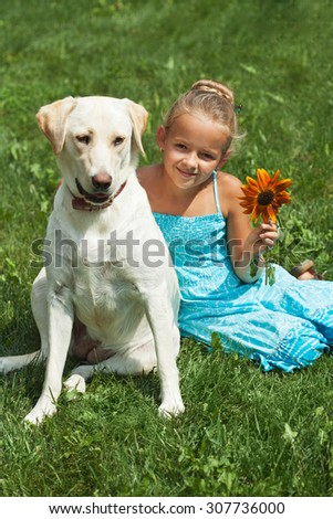 Young girl sitting in the grass with her labrador dog - stock photo