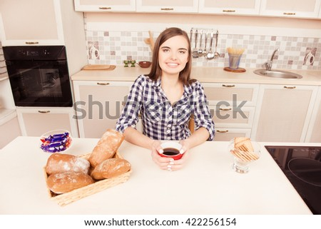 Young girl sitting in the kitchen and eating bun with tea
