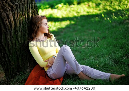 young girl sitting in the shade of a tree and enjoy the beauty of nature - stock photo