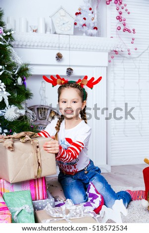 Young girl sitting near the Christmas tree in the studio with New Year decorations. A lot of toys. Christmas and New Year concept