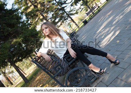 Young girl sitting on a bench in autumn park