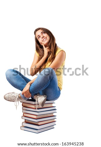 young girl sitting on a books tower isolated on white - stock photo