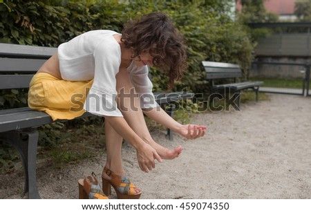 Young Girl Sitting on a Park Bench, Cleaning Her Foot Before Putting Her Shoes On