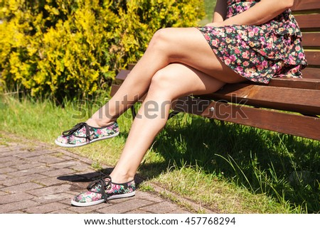 young girl sitting on a park bench on sunny summer day. legs closeup