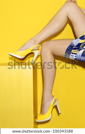 young girl sitting on cubes-yellow background - stock photo
