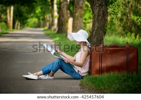 young girl sitting on empty asphalt road near old vintage leather suitcase reading the map - stock photo