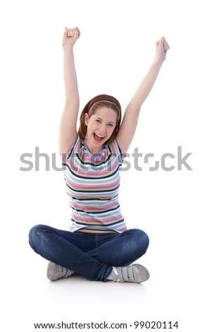 Young girl sitting on floor in tailor seat, stretching hands towards the sky, shouting happily. - stock photo