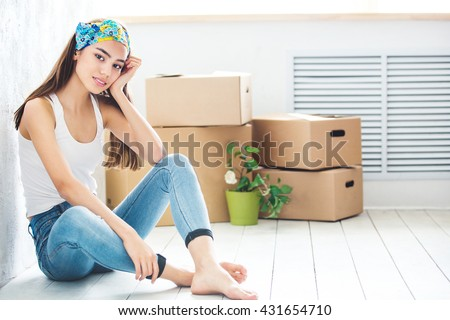 young girl sitting on floor with boxes for moving - stock photo