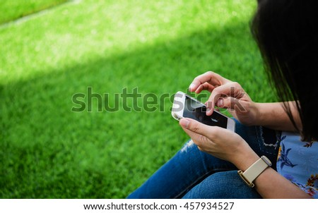 Young girl sitting on green grass with mobile phone.woman using her Mobile Phone. female student reading text messages on her mobile phone.