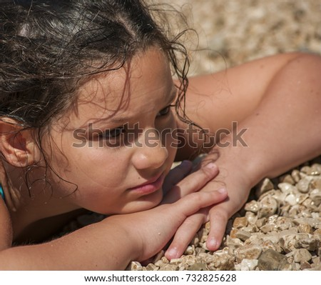 Young girl sitting on pebble beach