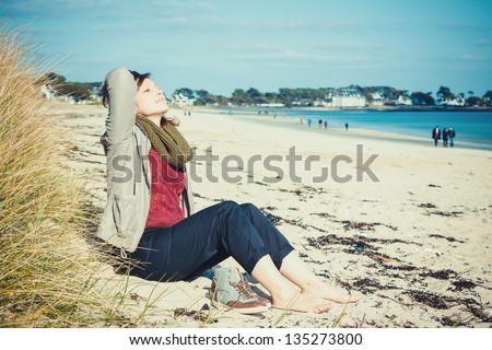Young girl sitting on the beach in early spring and enjoy the sun - stock photo