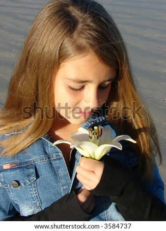 Young girl sitting on the beach, looking a a flower