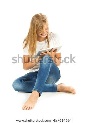 Young girl sitting on the floor using tablet pc over white background