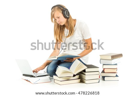 Young girl sitting on the floor with books and laptop over white background