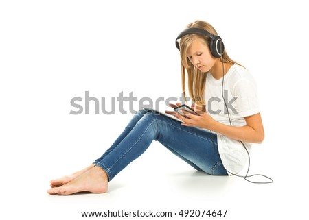 Young girl sitting on the floor with tablet pc, smartphone and headphones over white background