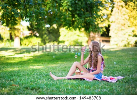 Young girl sitting on the grass and blowing bubbles - stock photo