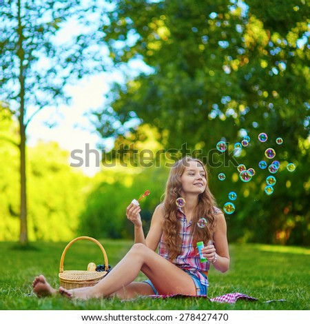 Young girl sitting on the grass and blowing bubbles on a summer day - stock photo