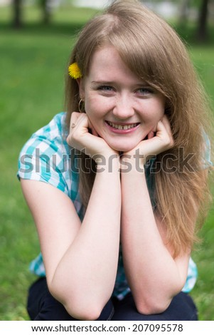 young girl sitting on the grass with dandelion in the teeth - stock photo