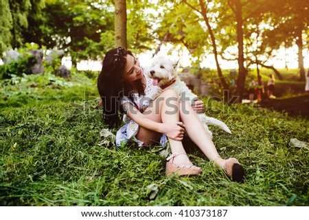 young girl sitting on the lawn with her dog