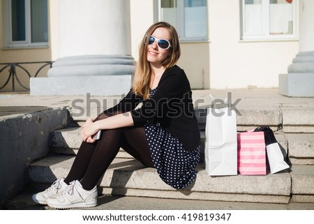 Young girl sitting on the steps with shopping bags