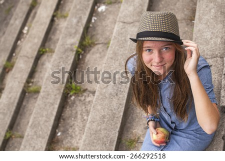 Young girl sitting on the stone steps of the old park. - stock photo